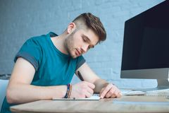 focused young man writing in notebook while working stock photo