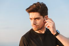 Focused young sportsman in black t-shirt in earphones royalty free stock photo