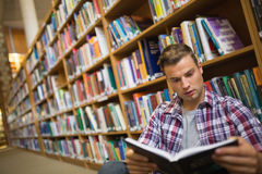Focused young student sitting on library floor reading book Royalty Free Stock Photography