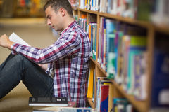 Focused young student sitting on library floor reading. In college Royalty Free Stock Images