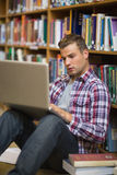 Focused young student sitting on library floor using laptop Stock Photo
