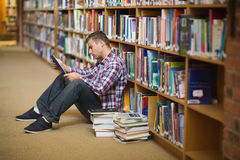 Focused young student sitting on library floor using tablet. In college Stock Photos