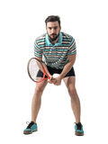 Focused young tennis player waiting to return serve holding racket with both hands. Full body length portrait isolated over white studio background Royalty Free Stock Photography