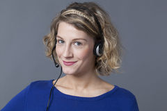 Focused young woman using headset for answering phone call Royalty Free Stock Photo