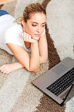 Focused young woman using laptop while lying on floor Stock Photo