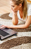 Focused young woman using laptop while lying on floor Stock Images