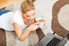 Focused young woman using laptop while lying on floor and drinking coffee Stock Photos