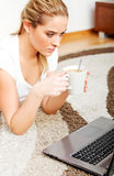 Focused young woman using laptop while lying on floor and drinking coffee Royalty Free Stock Image