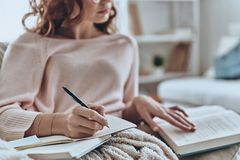 Focusing on education. Close up of young woman writing something down while sitting on the sofa at home stock photos