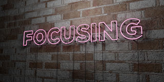 FOCUSING - Glowing Neon Sign on stonework wall - 3D rendered royalty free stock illustration Stock Photos