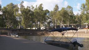 Lens readjusts and focuses on the three boats behind. A focusing, long shot readjusting from a wooden billboard to three boats docked at the station behind stock footage
