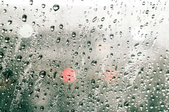 Focusing on the rain droplets, tailights out of focus,Rainy nigh. T traffic ,lights in the raindrops on a car windscreen form a colorful background.Bangkok Royalty Free Stock Image
