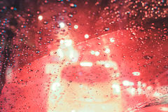 Focusing on the rain droplets, tailights out of focus,Rainy nigh. T traffic ,lights in the raindrops on a car windscreen form a colorful background.Bangkok Stock Photo