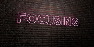 FOCUSING -Realistic Neon Sign on Brick Wall background - 3D rendered royalty free stock image. Can be used for online banner ads and direct mailers Royalty Free Stock Images