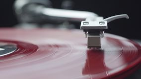 Focusing on red vinyl record on the turntable player. Focusing on red vintage vinyl record on the turntable player stock footage