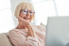 Focusing on something. Beautiful senior woman using laptop and smiling while relaxing on the couch at home stock photo