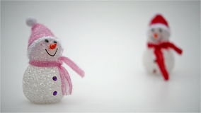 Focusing to two toy christmas snowman stock video