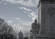 Focusing on the U.S. Capitol Dome. Sculpture on the Christopher Columbus monument appears to have his stony gaze focused on the U.S. Capitol dome, now under Royalty Free Stock Photos