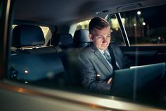 Focusing on work- businessman working on his laptop on the back seat of the car. Focusing on work- serious businessman working on his laptop on the back seat of stock photo