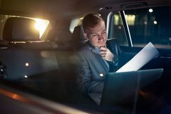 Focusing on work- businessman working on his laptop and paper on the back seat of the car. Focusing on work- serious businessman working on his laptop and paper royalty free stock photo