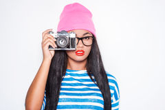Focusing at you. Attractive young African woman in funky clothes focusing at you with her old-fashioned camera while standing against white background Royalty Free Stock Photo