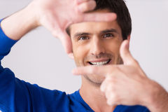 Focusing at you. Playful young man in blue sweater gesturing finger frame and smiling while standing against grey background Royalty Free Stock Photos