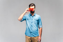 Focusing at you. Studio shot of handsome young man in casual wear holding retro camera near face and focusing at you Royalty Free Stock Image