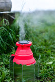 Fodable camping kettle with boiling water standing on burning stove. Royalty Free Stock Photos