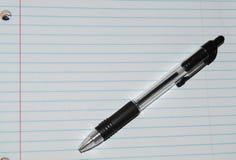 Fodrat vitt anteckningsbokpapper med en svart penna Royaltyfri Foto