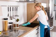 Fogão da indução da limpeza da mulher na cozinha fotografia de stock