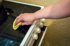 Fogão da limpeza da mulher em sua cozinha imagens de stock