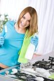 Fogão da limpeza da mulher nova na cozinha moderna Imagem de Stock