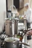 Fogão de Heating Saucepan On do cozinheiro chefe imagem de stock