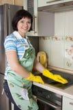 Fogão de sorriso da limpeza da mulher Fotografia de Stock Royalty Free