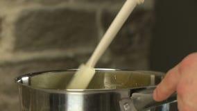 Fogão que agita o syrop na bacia com espátula da cozinha video estoque
