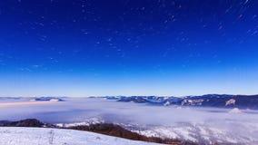 Fog двигать над горой в зиме с звездообразным небом видеоматериал