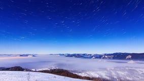 Fog двигать над горой в зиме с звездообразным небом сток-видео