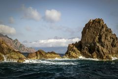 Fog at the back and rock formations in the turbulent sea on the coast of the island. Of Corsica stock photos