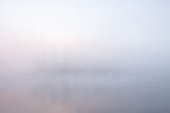 Fog dreamy background. Nature dreamy foggy (misty) background scenery: trees and their reflections in water surface (lake, river, pond) visible through fog (mist stock photography