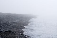 Fog on the Baikal spring sunrise stony beach Stock Image