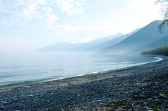 Fog on the Baikal spring sunrise stony beach Royalty Free Stock Photo