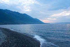 Fog on the Baikal spring sunrise stony beach Royalty Free Stock Photos