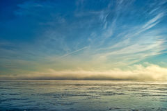 Fog bank on Penobscot River Maine. A fog bank rolling in on the Penobscot River in Stockton Springs Maine with ice and streaked sky Royalty Free Stock Images