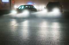 Fog on city streets. Cars driving through fog on city streets Stock Images