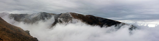 Fog climbing up the mountain Stock Photo