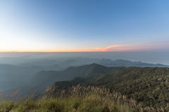 Fog covered forest and mountain at sunset.  Royalty Free Stock Image