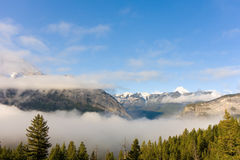 A fog-covered valley surrounded by mountains in the springtime Royalty Free Stock Photo