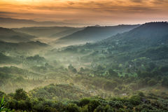 Fog at dawn over the valley in Tuscany Stock Image