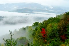 Fog floats across the mountain on a fall day. Royalty Free Stock Photo