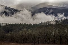 Fog floats around the mountains and fields of Cades Cove. Stock Photo